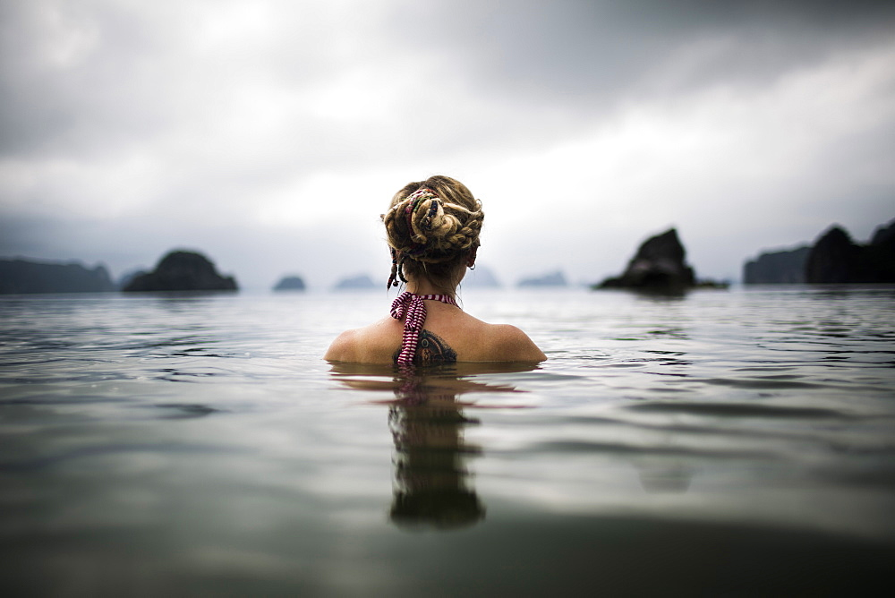 Rear view of woman with blond braided hair wading into the ocean, Vietnam