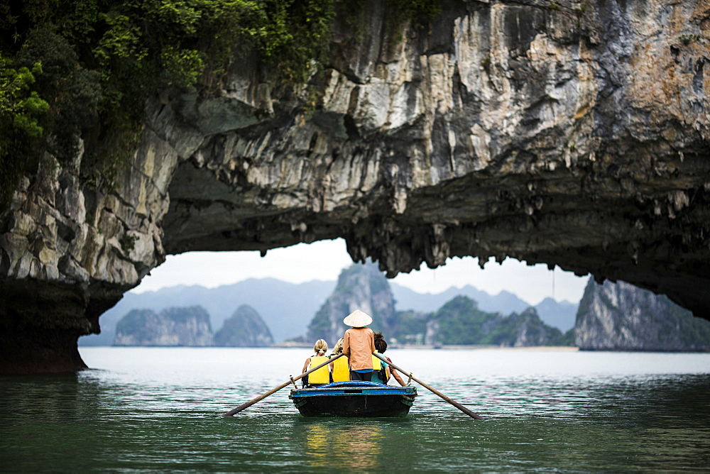 Rear view of man wearing straw hat transporting small group of people on a boat, rowing underneath natural rock arch, Vietnam
