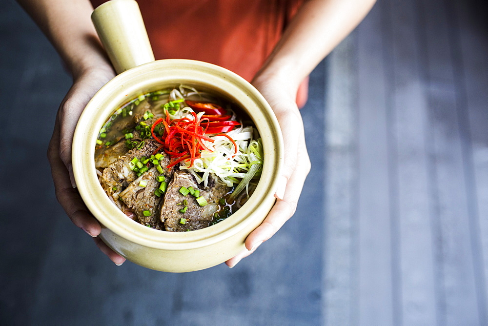 High angle close up of person holding bowl of Bun Bo Hue, Vietnam
