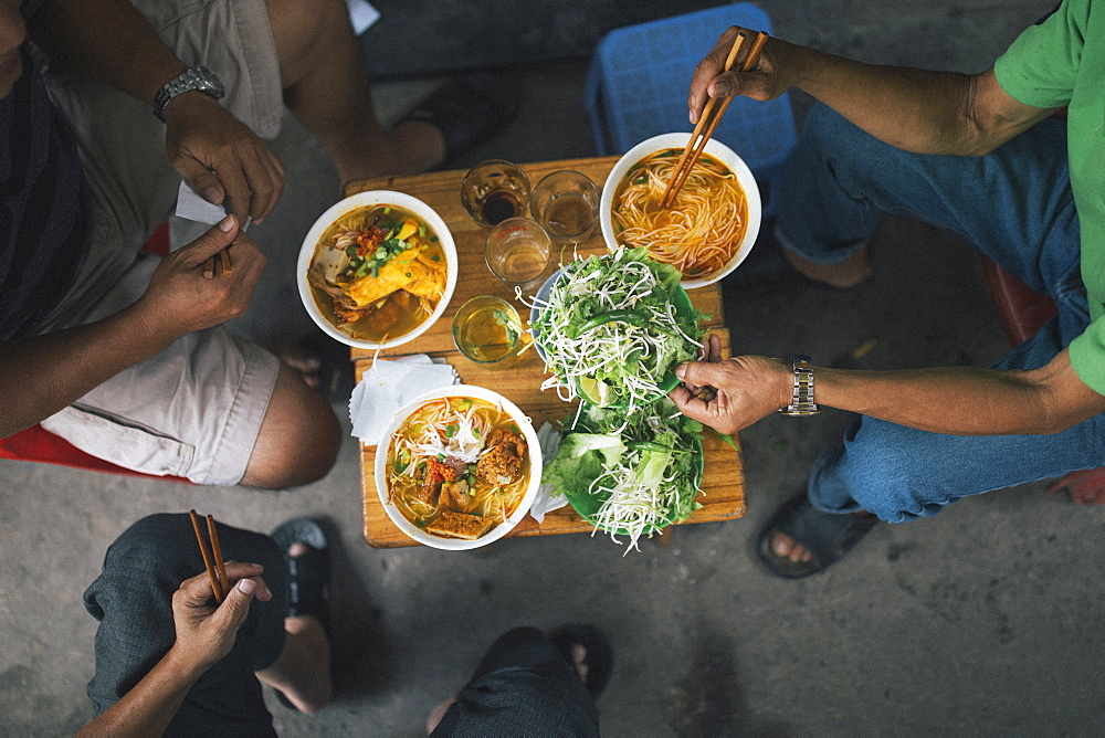 High angle close up of three men tucking into bowls of noodles for breakfast in a small alleyway, Vietnam