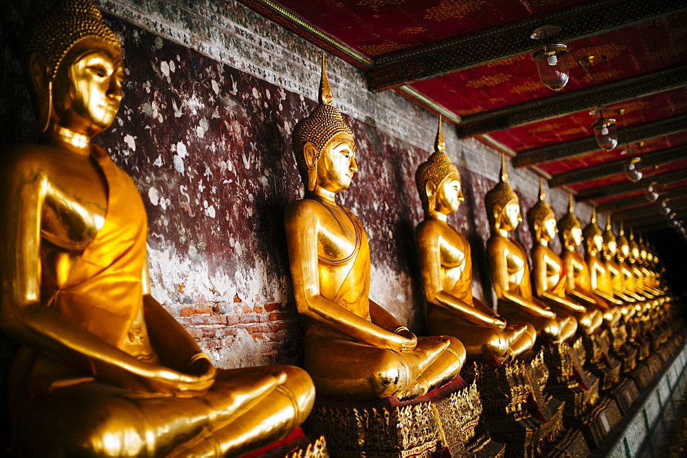Close up of a row of golden Buddha statues along a wall, Thailand