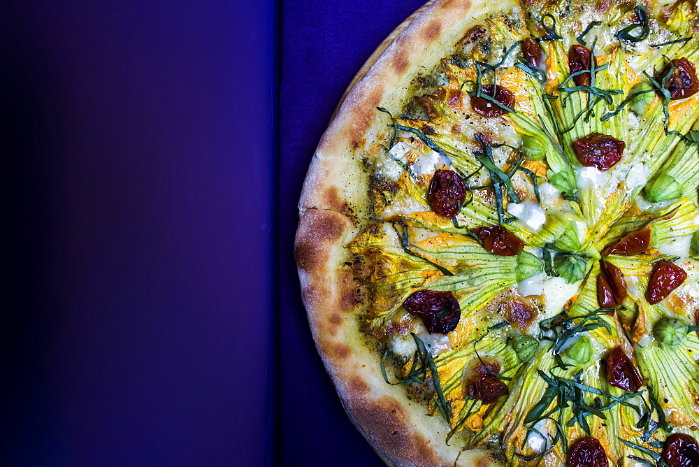 High angle close up of vegetarian pizza with goat cheese and zucchini flowers, Vietnam