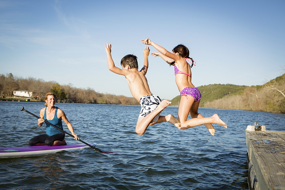 Two children leaping into the water from a jetty, Austin, Texas, USA