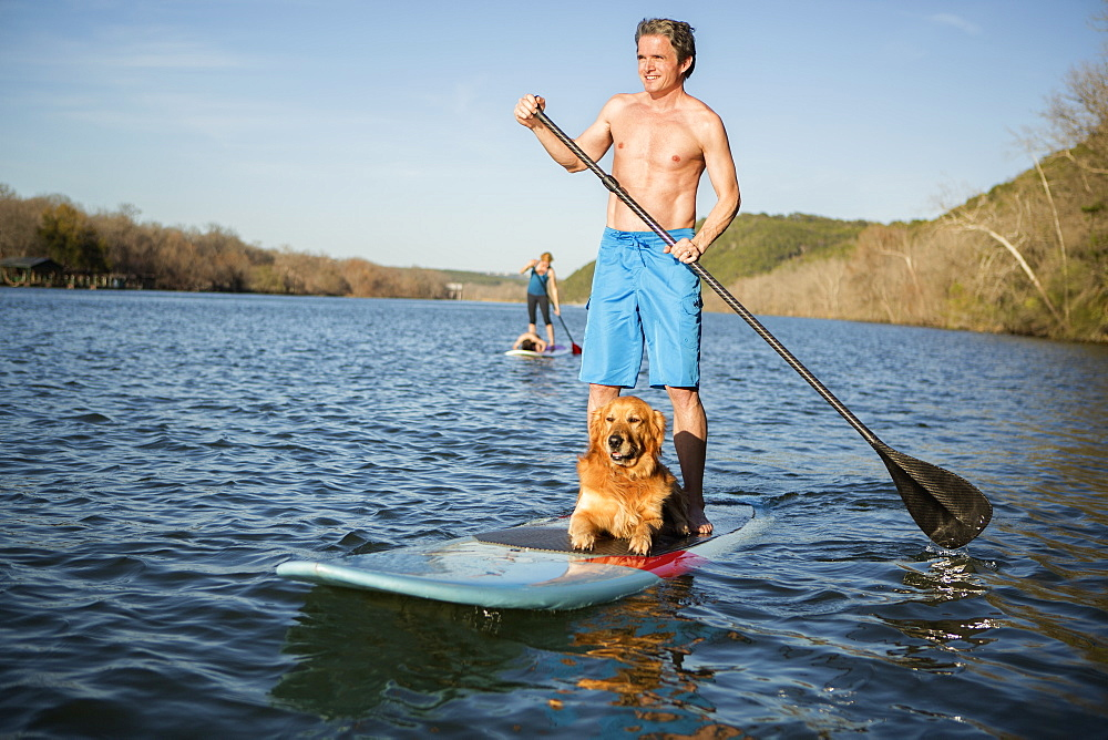 A man standing on a paddleboard with a dog, Austin, Texas, USA