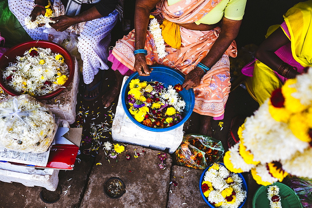 High angle close up of women lacing flowers on strings at a market, India