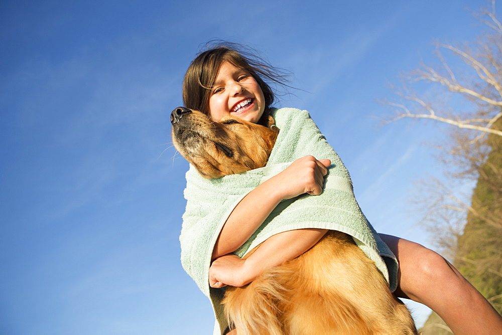 A girl in a beach towel with a golden retriever dog, Austin, Texas, USA