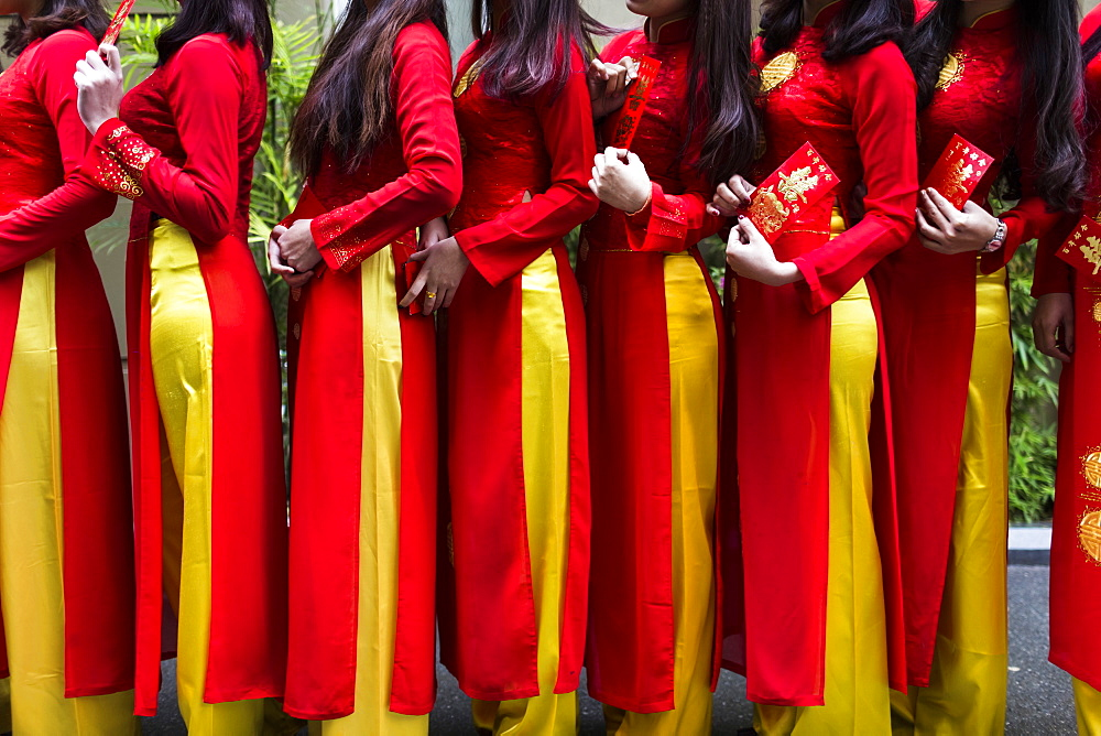Close up of line of young women in traditional red and yellow dress outside of a wedding, Vietnam