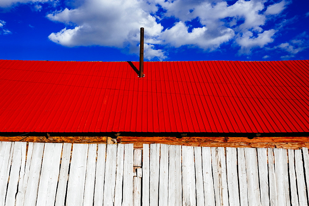 Low angle close up of white wooden building with bright red roof under a cloudy sky, Mongolia
