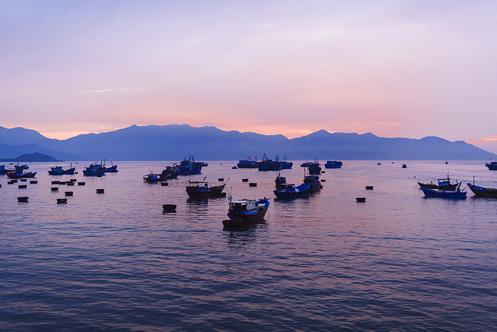 Large group of fisherman in traditional fishing boats on lake at sunrise, mountains in the distance, Vietnam