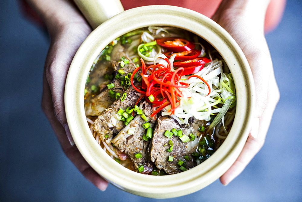 High angle close up of hands holding bowl with Asian soup containing rice vermicelli, beef and chili garnish, Vietnam