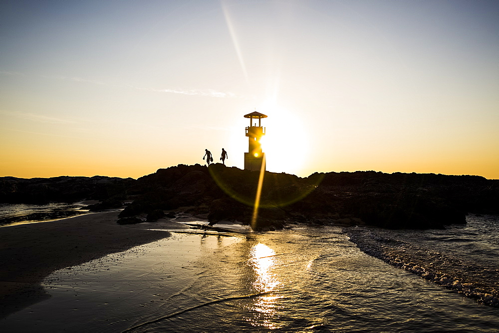 Silhouette of two people walking past lighthouse by the ocean at sunset, Thailand