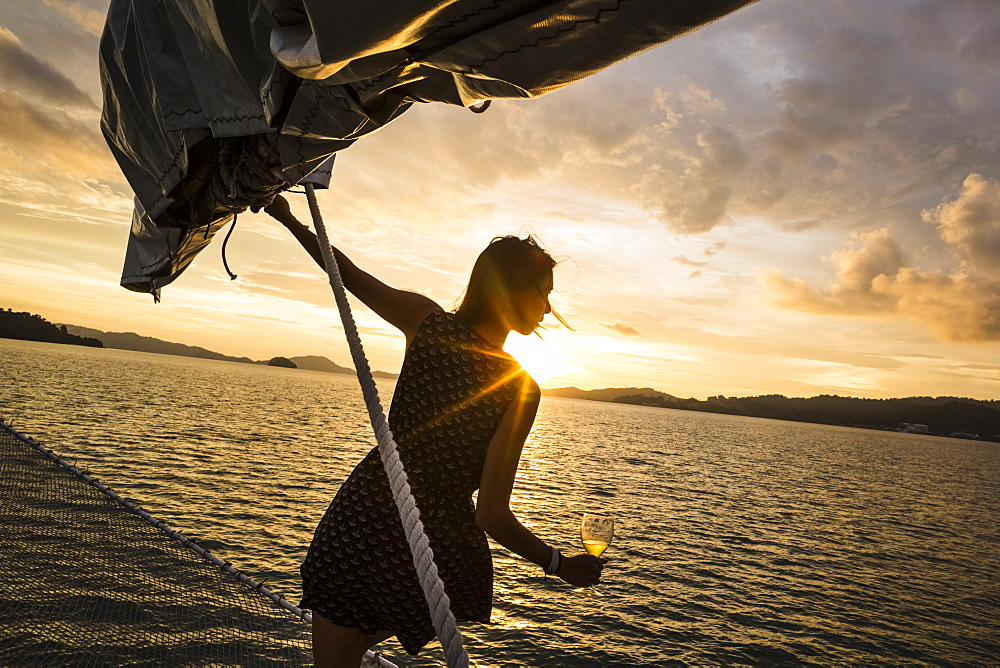 Woman holding wine glass standing on board a boat, sunset dinner cruise on Indian Ocean, Malaysia