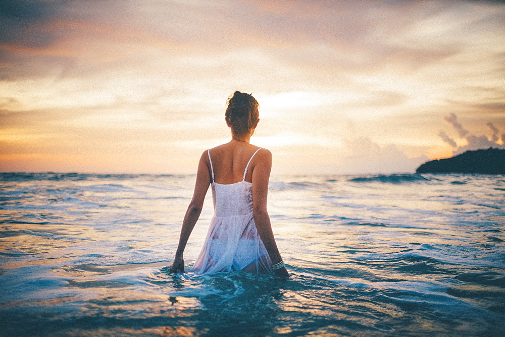 Rear view of young woman wearing a white dress walking in the ocean at sunset, Thailand
