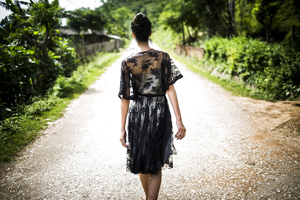 Rear view of woman wearing black lace dress walking down a rural country road, Vietnam
