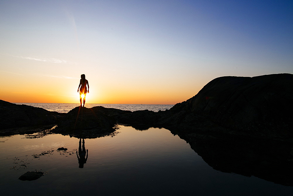 Silhouette of woman standing on a rock by the ocean at sunset