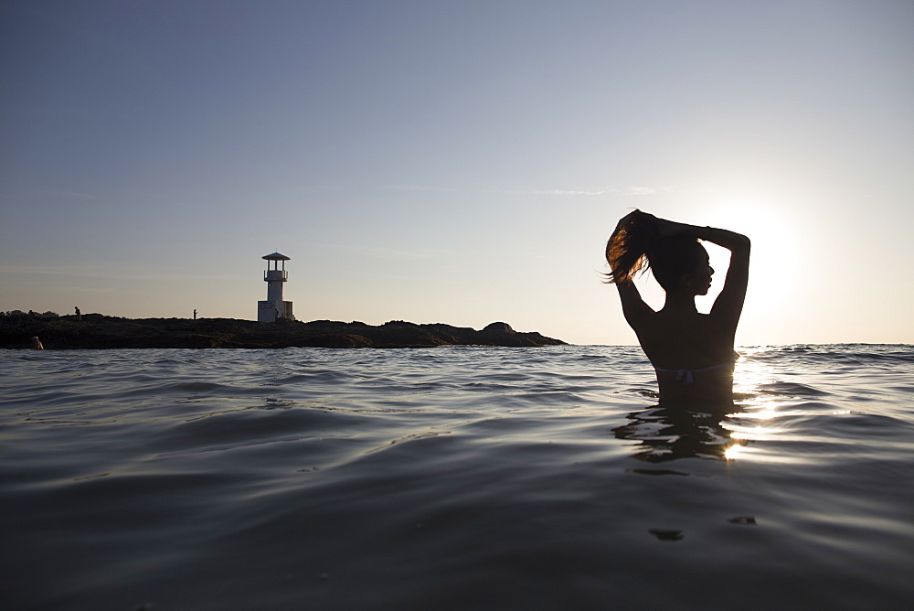 Rear view of woman bathing in the ocean at sunset, lighthouse in the distance