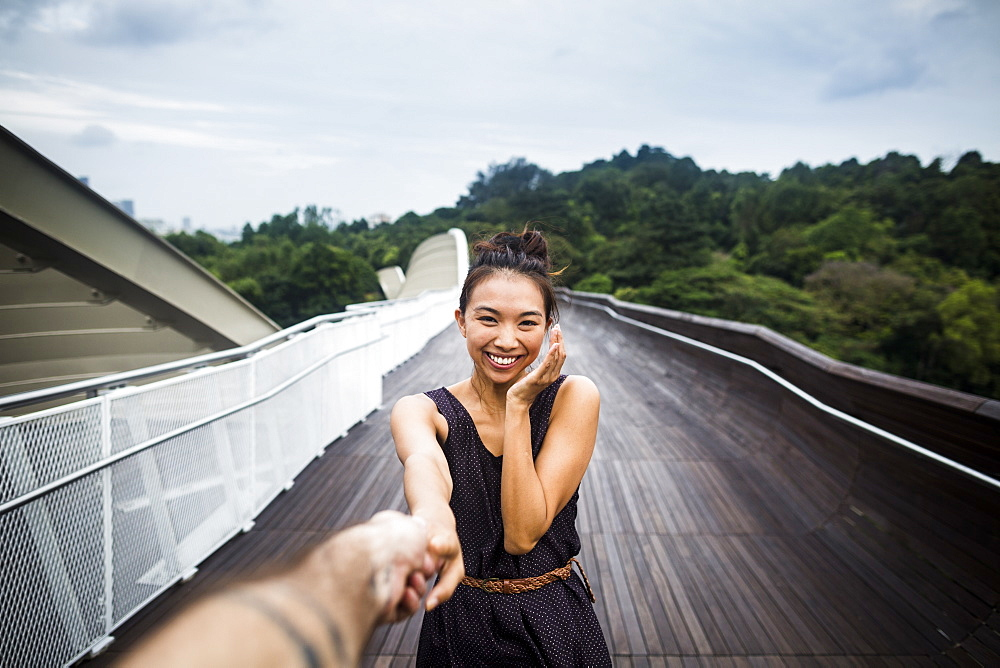 Smiling young woman standing on a bridge, holding man's hand, Singapore - 1174-7653