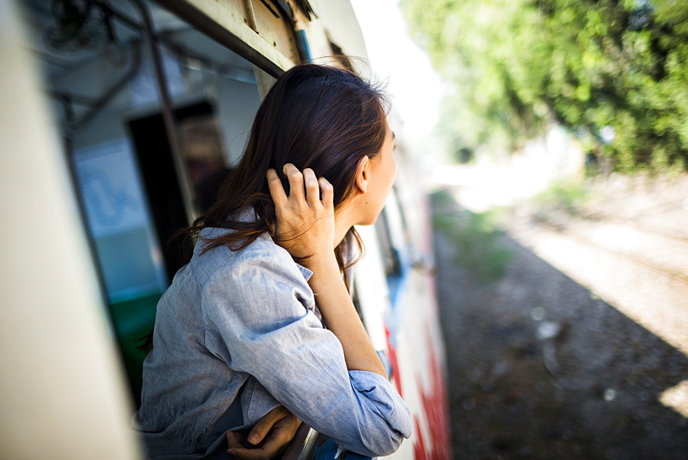 Young woman riding on a train, looking out of window, Myanmar