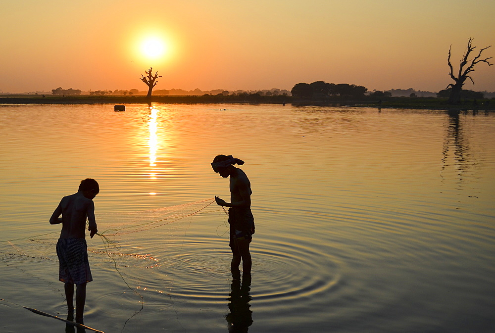 Two boys fishing in a lake at sunset, Amapura, Myanmar, Amapura, Myanmar