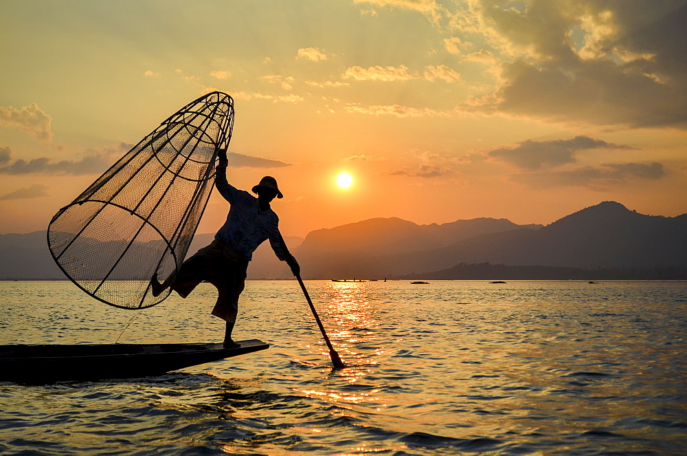 A fisherman balancing on one leg on a boat, holding a large fishing basket, fishing in the traditional way on Lake Inle at sunset, Myanmar