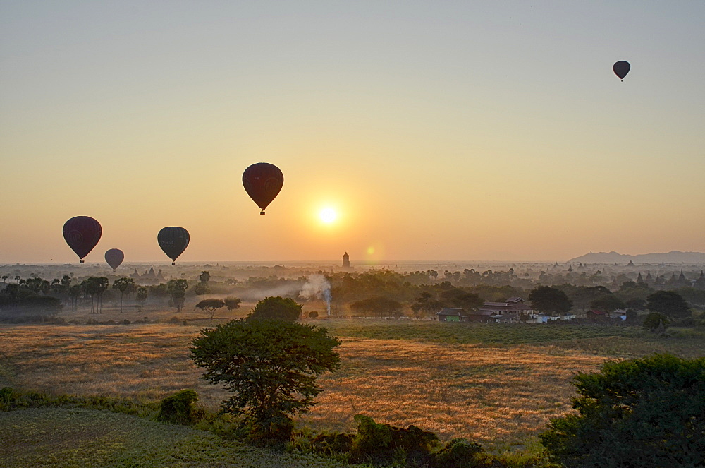 Hot air balloons over landscape with distant temples at sunset, Bagan, Myanmar
