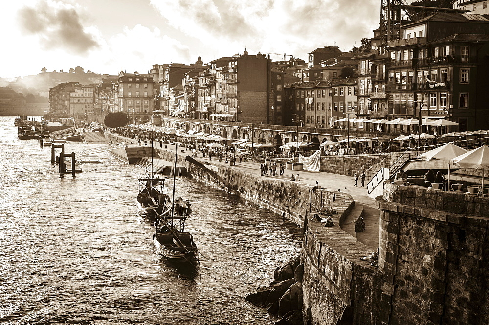 Port boats and freight barges moored beside a waterfront wall, and people on the promenade. Historic buildings, Porto, Portugal