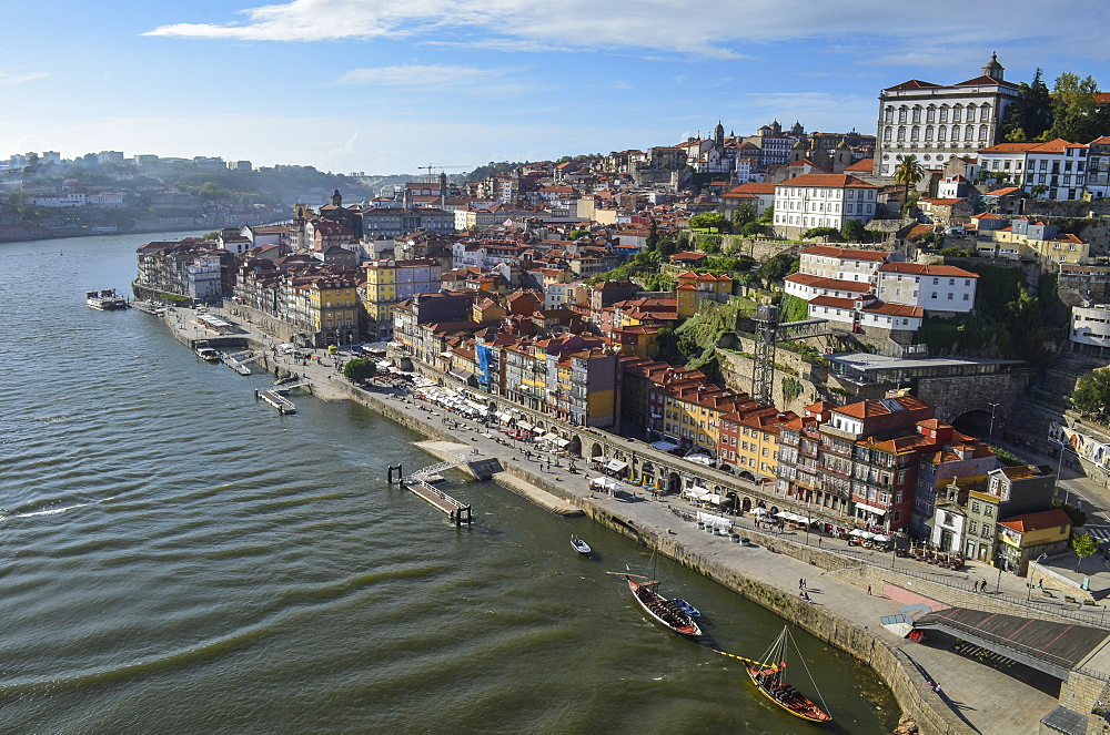 High angle view of coastal town with sailboat moored near harbour wall, Portugal