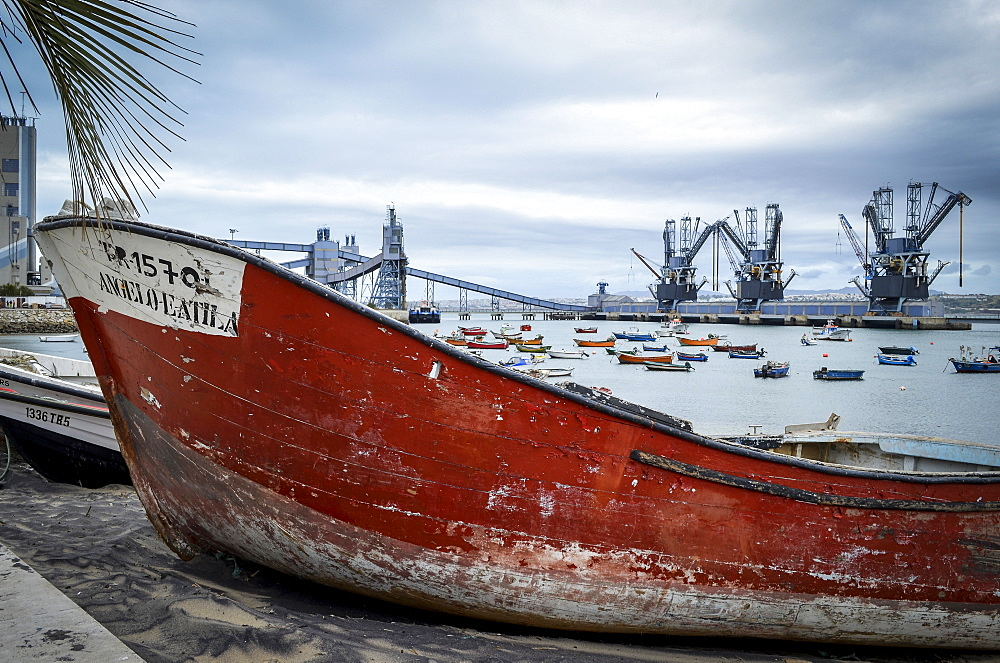 An old boat with a red shabby hull beached on the shore by the water in Lisbon. Shipping cranes and a large modern road bridge in the distance, Lisbon, Portugal