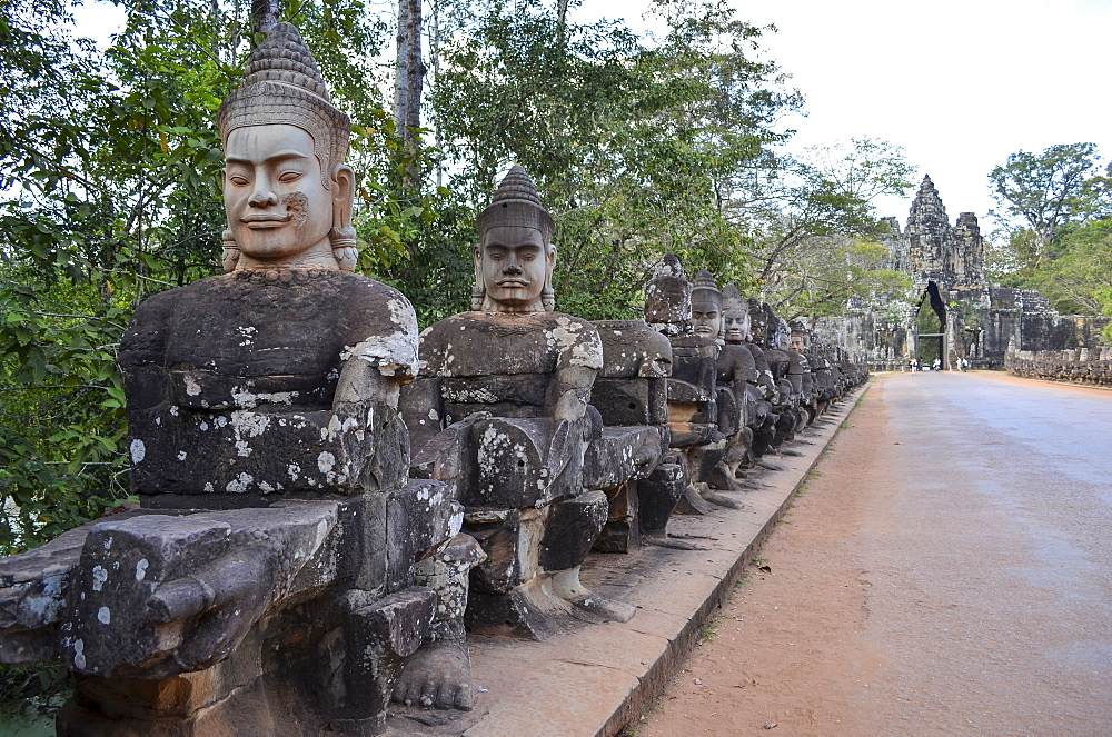 Ankor Wat, a 12th century historic Khmer temple and UNESCO world heritage site. Busts and statues of deities and guardian figures along a path to a stupa and entrance arch, Angkor Wat, Cambodia