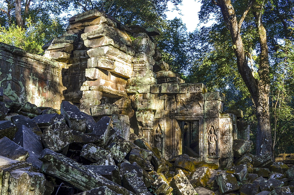 Ankor Wat, a 12th century historic Khmer temple and UNESCO world heritage site. Arches and carved stone blocks in ruins of temple pavilions, with trees dominating the buildings, Angkor Wat, Cambodia