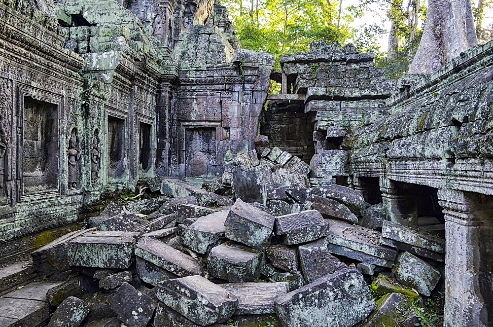 Ankor Wat, a 12th century historic Khmer temple and UNESCO world heritage site. Arches and carved stone blocks, fallen masonry and structures being overgrown by the jungle, Angkor Wat, Cambodia