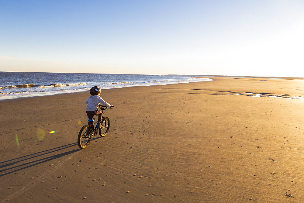 A young boy riding a bicycle on the beach, St Simon's Island, Georgia, United States