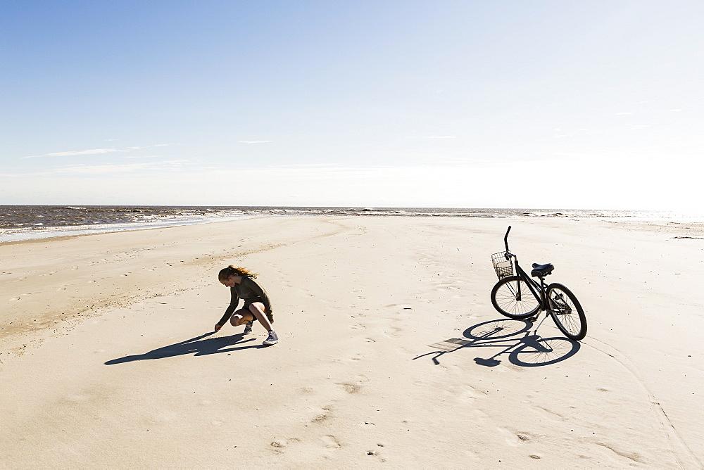 A teenage girl on a wide empty sandy beach collecting shells, St Simon's Island, Georgia, United States