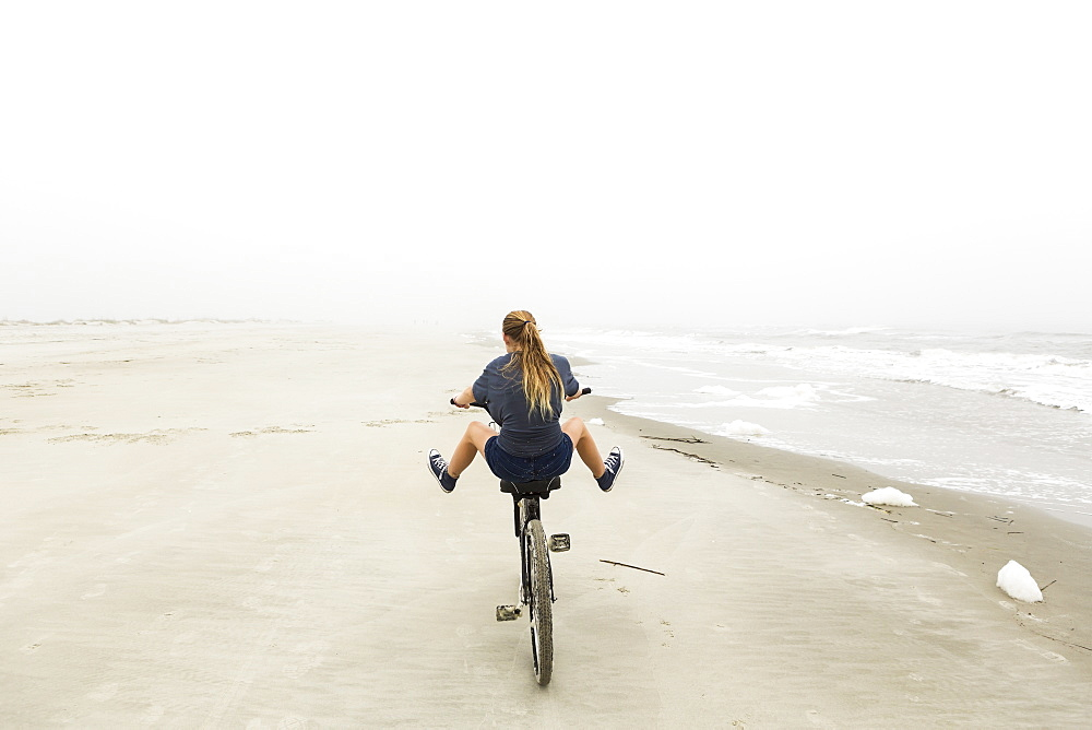 Teenage girl riding a bike on sand at the beach, St Simon's Island, Georgia, United States
