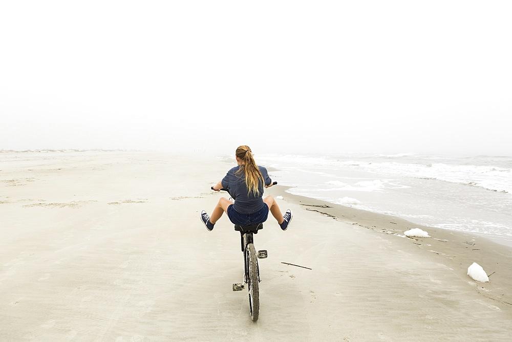 Teenage girl riding a bike on sand at the beach, St Simon's Island, Georgia, United States - 1174-7746