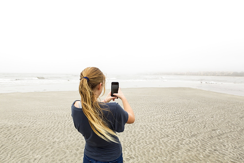 A teenage girl talking pictures with smart phone at the beach, St Simon's Island, Georgia, United States
