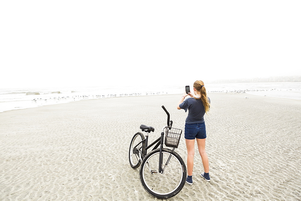 A teenage girl talking pictures with smart phone at the beach, St Simon's Island, Georgia, United States - 1174-7754
