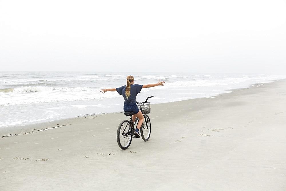 A teenage girl biking on a sandy beach by the ocean, St Simon's Island, Georgia, United States