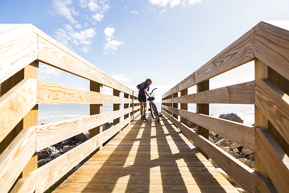 Teenage girl on wooden bridge with her bike, St Simon's Island, Georgia, United States