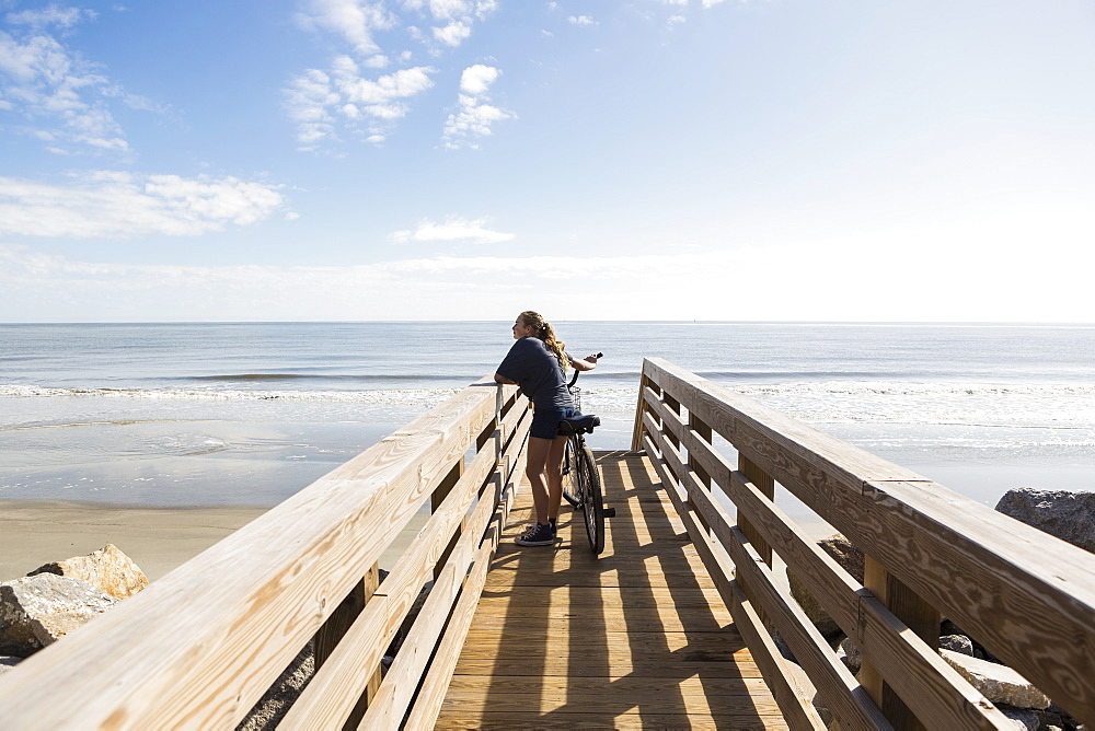 Teenage girl on wooden bridge by the beach, with her bike, St Simon's Island, Georgia, United States