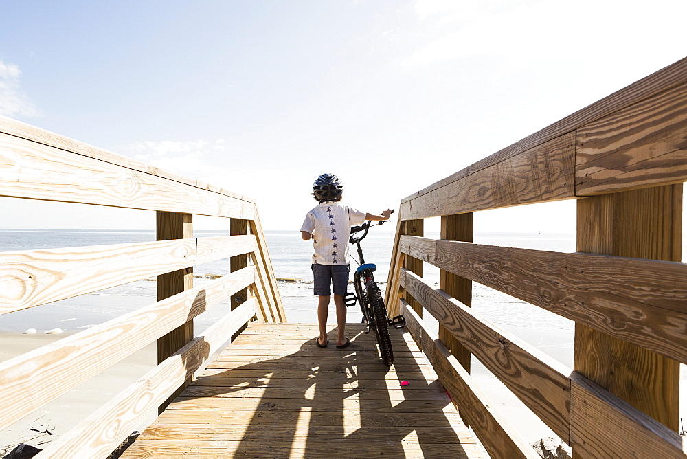 A young boy on wooden bridge with his bike, St Simon's Island, Georgia, United States