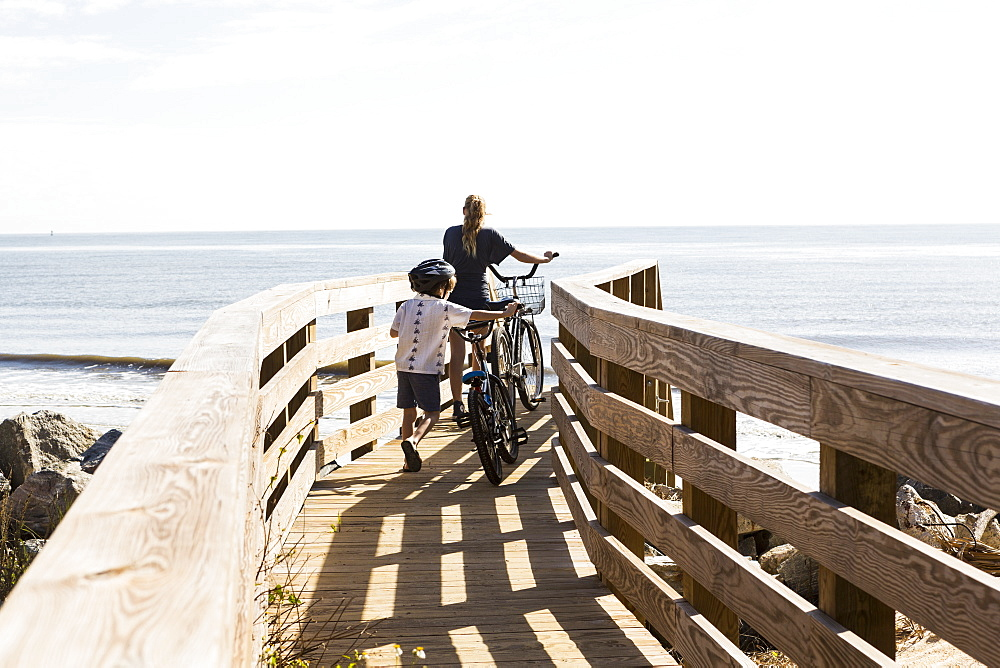 Two children, brother and sister on wooden bridge with bikes, St Simon's Island, Georgia, United States - 1174-7771