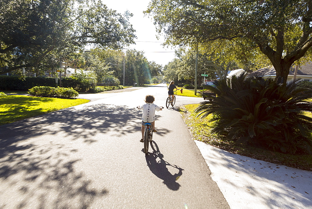 Children, a pre teenager and her brother cycling on a suburban road, St Simon's Island, Georgia, United States