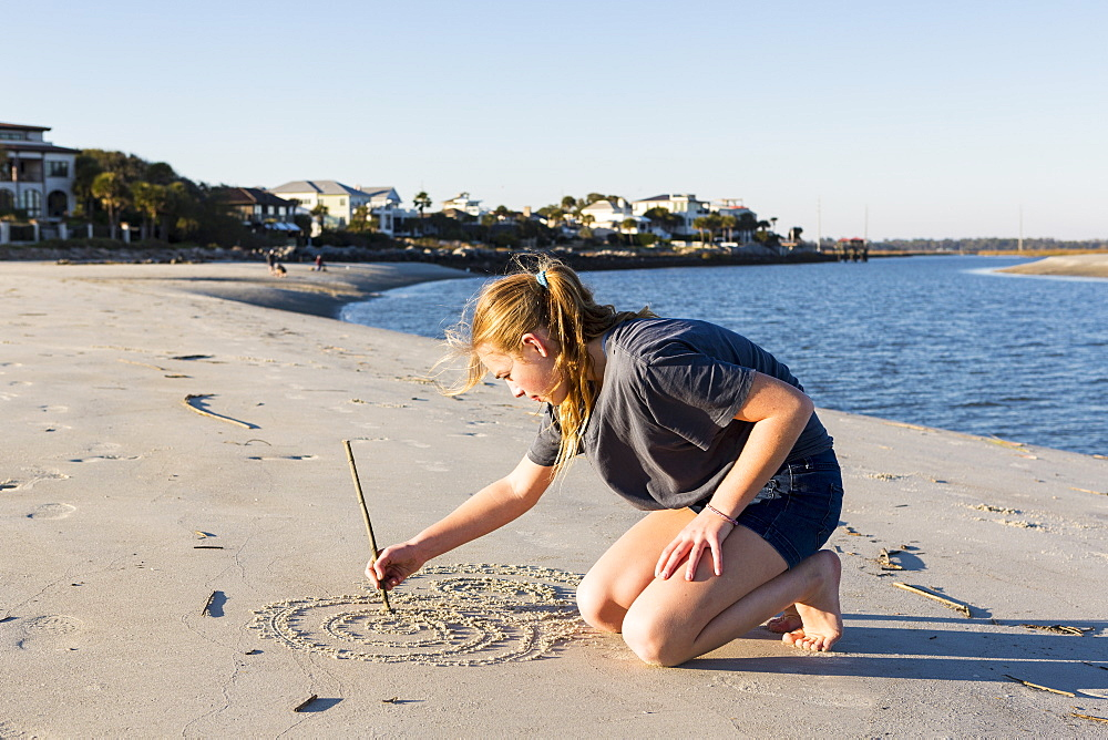 A teenage girl playing in sand dunes, at the beach, St Simon's Island, Georgia, United States