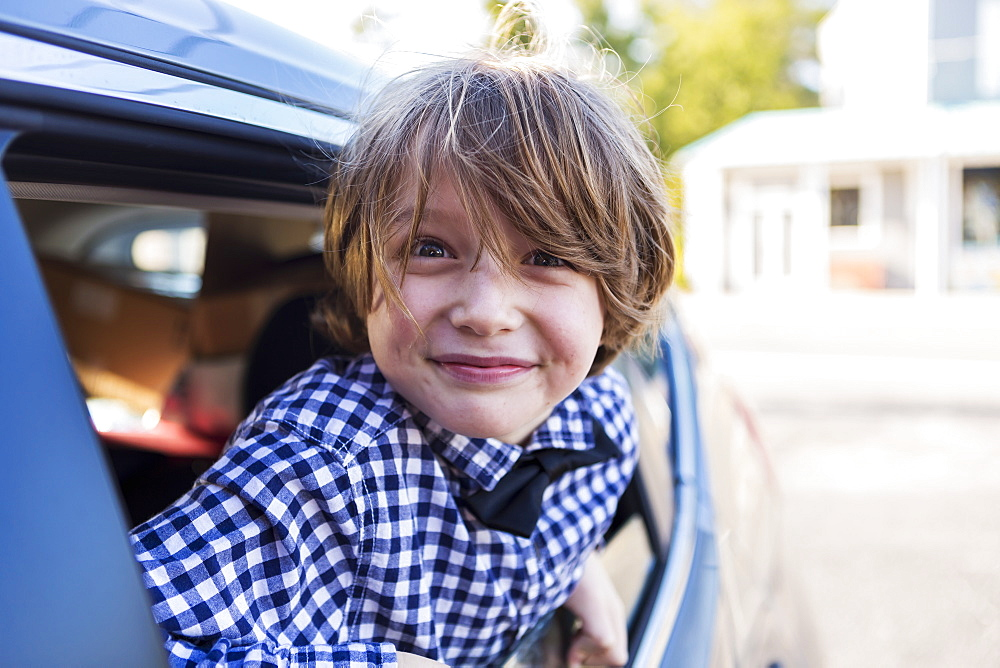 A six year old boy smiling at camera, looking out of car window, St Simon's Island, Georgia, United States - 1174-7782