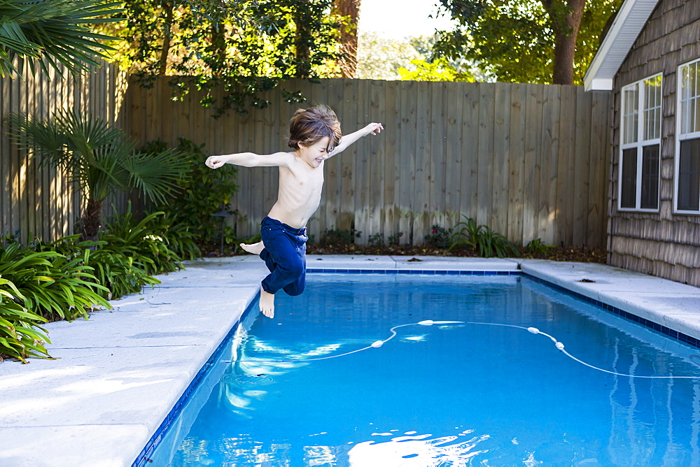 A six year old boy leaping into a swimming pool, St Simon's Island, Georgia, United States