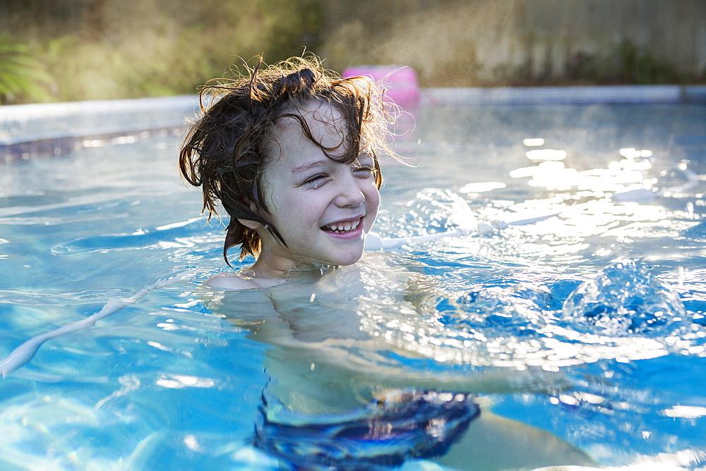 A six year old boy swimming in a warm pool, St Simon's Island, Georgia, United States