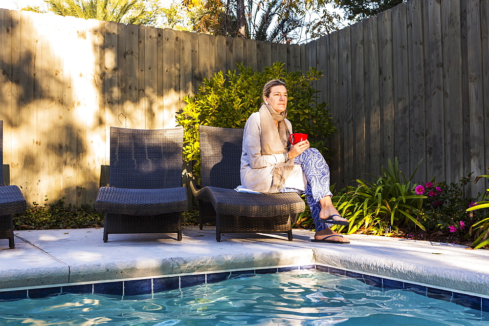 Woman sitting on sun lounger by a swimming pool, St Simon's Island, Georgia, United States