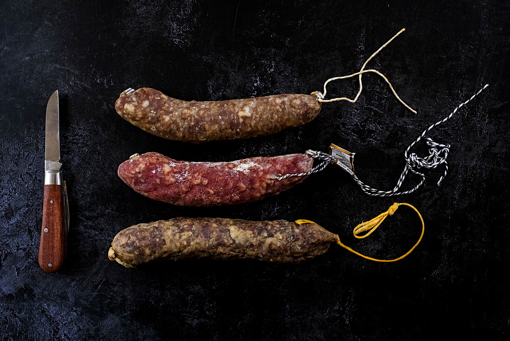 High angle close up of knife and selection of three salamis on black background, United Kingdom