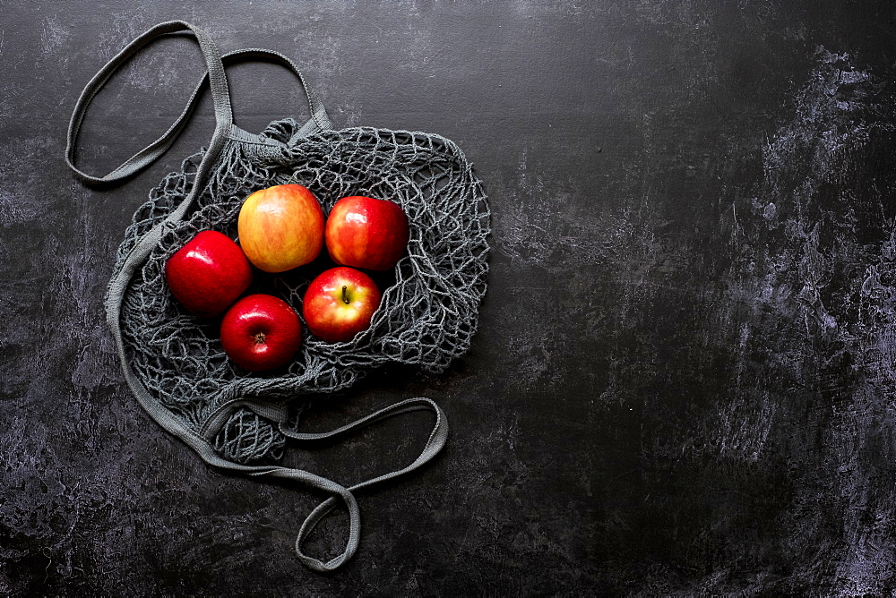 High angle close up of red apples in grey net bag on black background, United Kingdom - 1174-7830